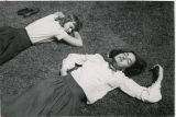 Two students lying on grass