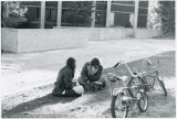 Two students and their bikes, in front of Erdman