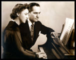 Publicity portrait of Fredric March and Florence Eldridge, seated at a piano, looking away