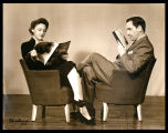 Publicity portrait of Fredric March and Florence Eldridge, seated in chairs, reading